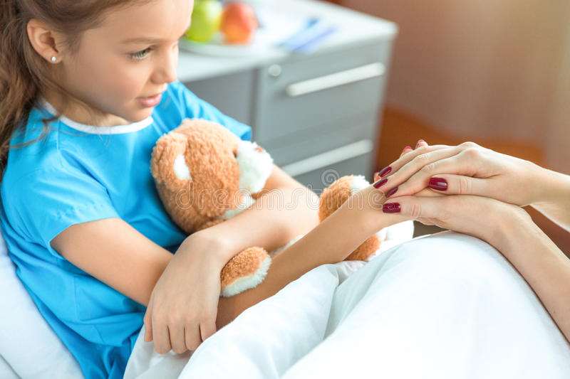 Doctor and little patient with teddy bear holding hands in hospital. Woman doctor and little patient with teddy bear holding hands in hospital royalty free stock photography