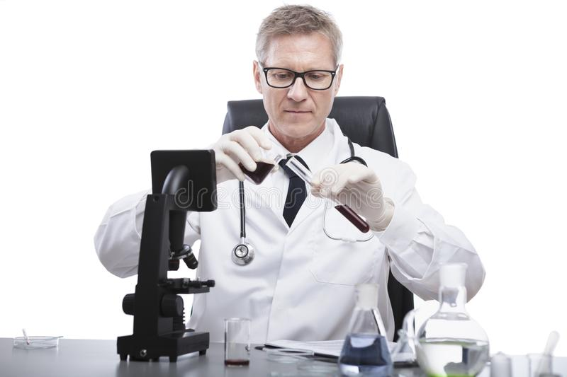 Doctor look and analyse blood test tube stock images