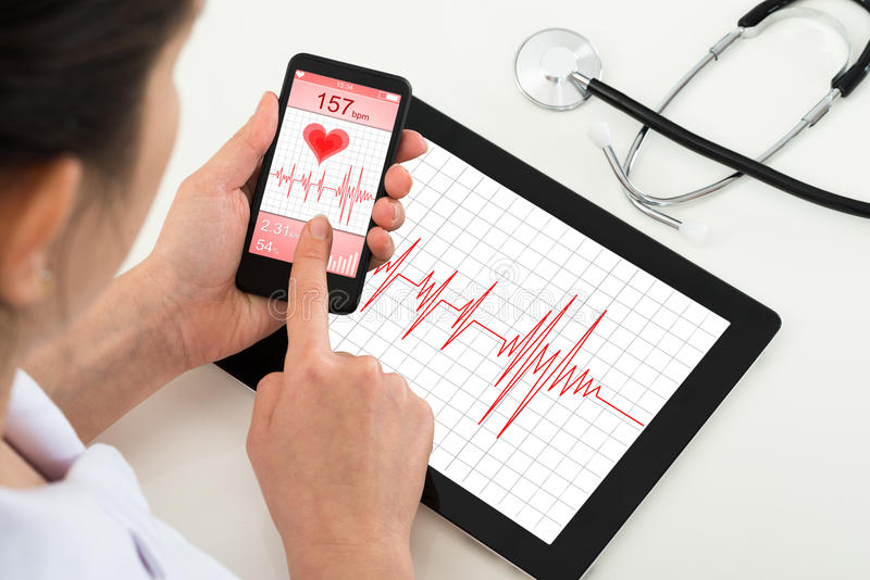 Doctor looking at app for health. Close-up Of Doctor Holding Mobile Phone With App For Health royalty free stock image