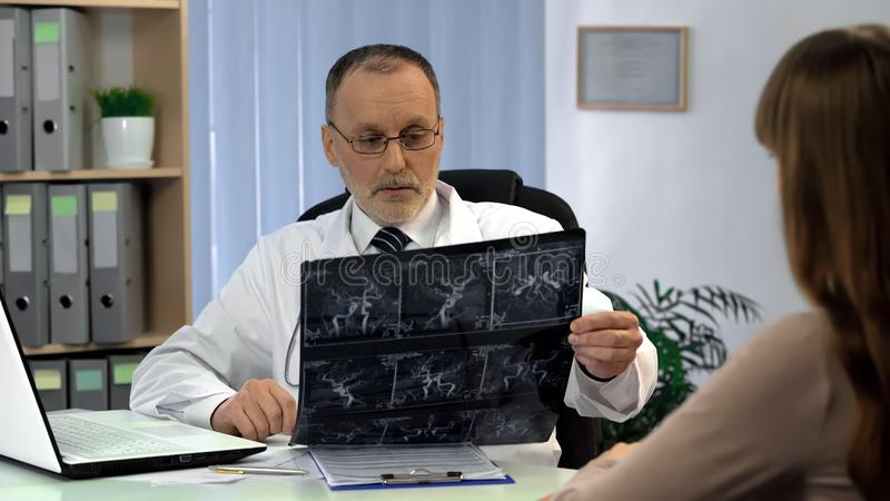 Doctor looking at blood vessels x-ray, diagnosis of thrombosis, varicose veins stock photos