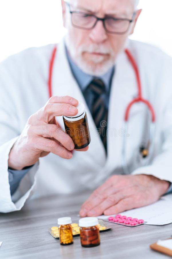 Doctor looking at a bottle of pills stock photo