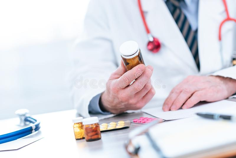 Doctor looking at a bottle of pills. In medical office stock photography
