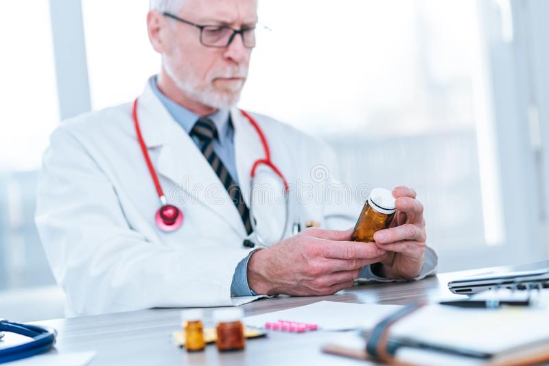 Doctor looking at a bottle of pills stock photography