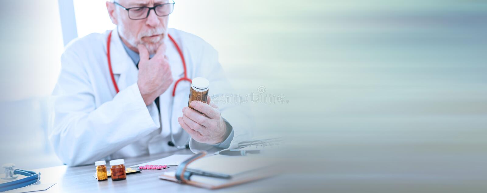 Doctor looking at a bottle of pills; panoramic banner. Doctor looking at a bottle of pills in medical office; panoramic banner stock images