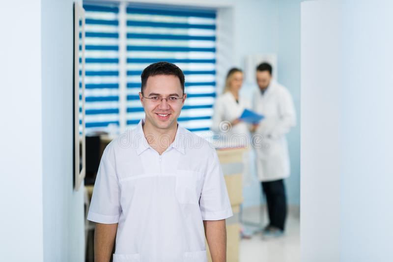 Doctor looking at camera while his colleague discussing in medical office royalty free stock images