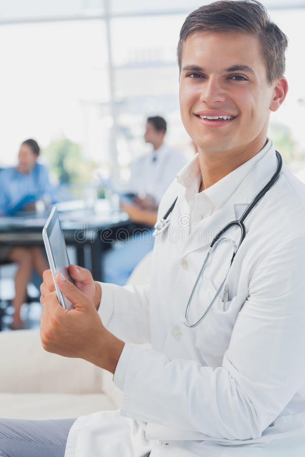 Download Doctor Looking At The Camera And Using Tablet Pc Stock Image - Image of brunette, scrolling: 32508965