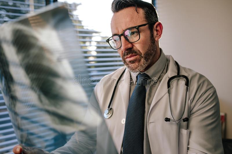 Doctor looking at chest x ray of his patient stock photos