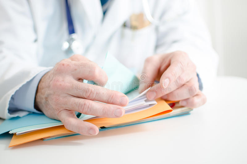 Doctor looking for a file. In his office royalty free stock image