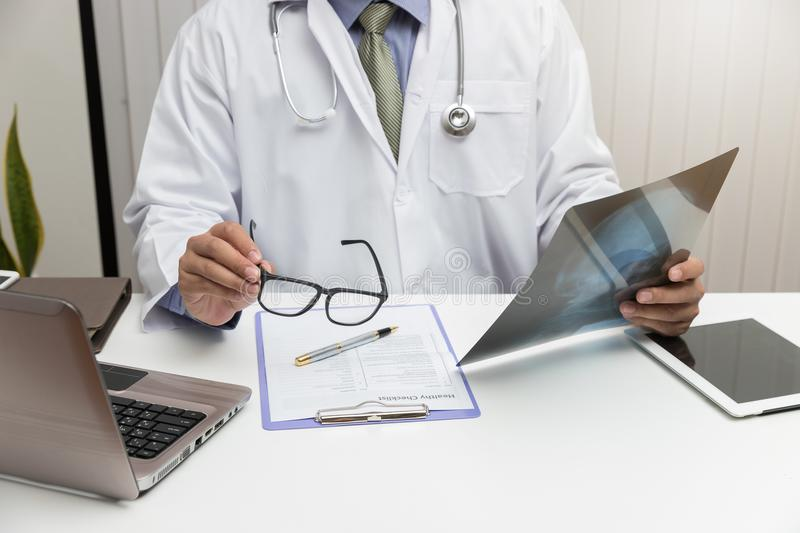 Doctor looking head x-ray film in office stock images