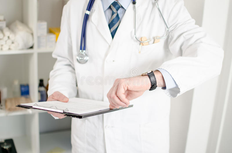 Doctor looking at his watch royalty free stock images