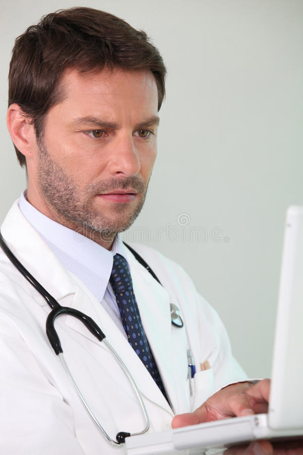 Doctor looking at laptop stock photos
