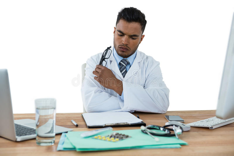 Doctor looking medical report at desk stock photography