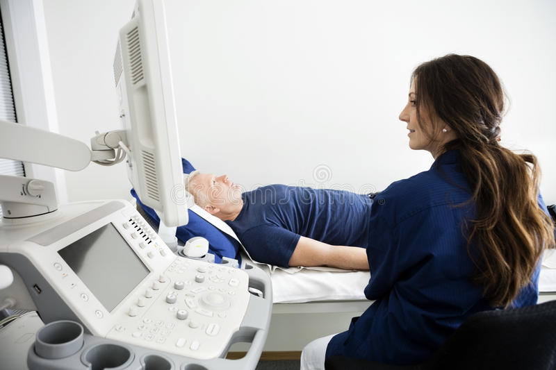 Doctor Looking At Monitor During Ultrasound Examination In Hospi. Mature female doctor looking at monitor during ultrasound examination in hospital royalty free stock photo