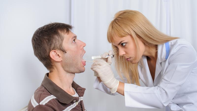 The doctor is looking in the mouth of the patient. Close view royalty free stock photos