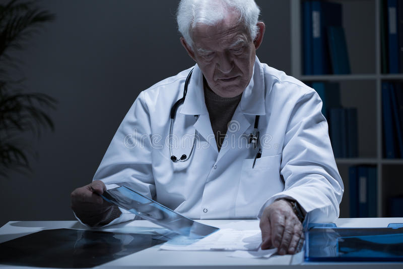 Doctor looking at x-ray image stock photography