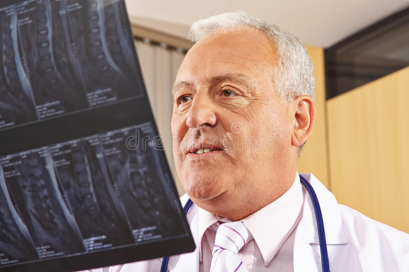 Doctor looking at x-ray image of spine. Doctor looking at an x-ray image of a human spine in a hospital royalty free stock images