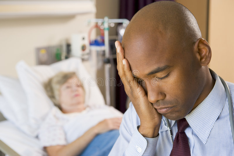 Doctor Looking Tired In Hospital Room stock images
