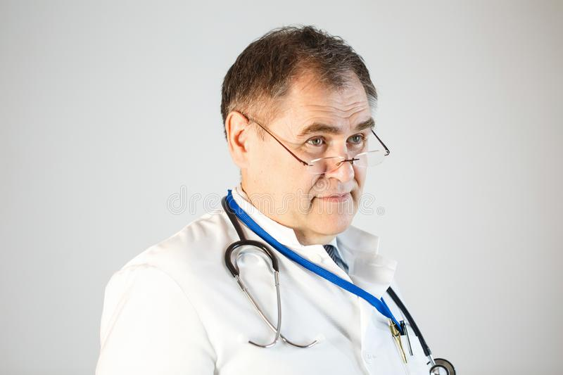 The doctor looks forward, glasses on the tip of his nose, eyebrows raised, a stethoscope and a badge hanging from his neck stock photo