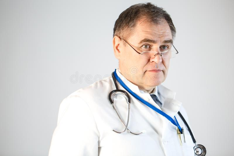 The doctor looks forward, pushing his glasses to the tip of his nose, a stethoscope and a badge hanging from his neck. Close up royalty free stock photo