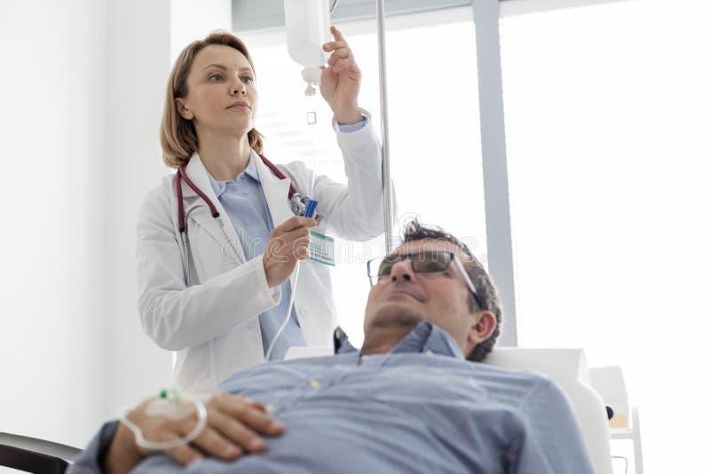 Doctor maduro que ajusta el goteo salino IV según paciente en sala de hospital fotografía de archivo libre de regalías