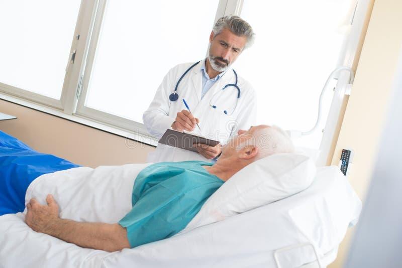 Doctor maduro que visita al paciente mayor en sitio de hospital fotografía de archivo