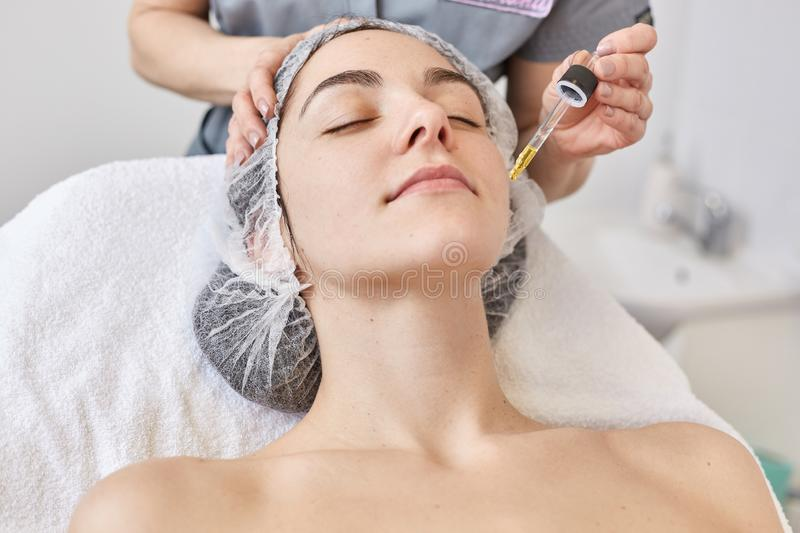 Doctor makes beautician procedure, applys vitamin serum to face of beautiful woman, client of cosmetology clinic. Young female royalty free stock photography