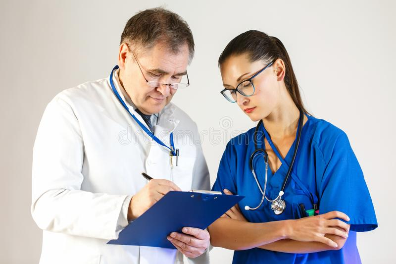 The doctor makes an entry in the patient`s card, the nurse stands next to him and looks. Close up stock images