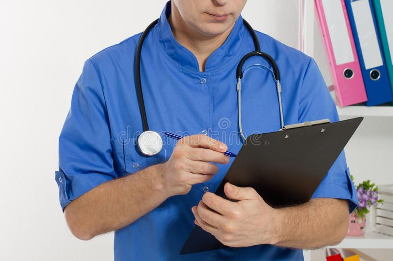Doctor makes notes in the clinic close up. Doctor working in medical office royalty free stock images