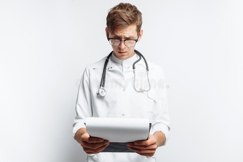 The doctor makes notes in the documents, a young student with a folder in his hands, on a white background royalty free stock image