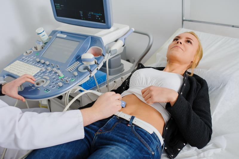 Doctor makes the patient women abdominal ultrasound. stock photography