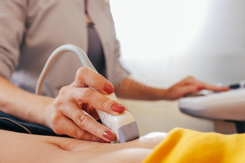 Doctor makes the patient women abdominal ultrasound. Ultrasound Scanner in the hands of a doctor. royalty free stock image