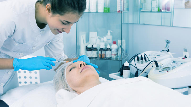 Doctor making injection. Woman doctor making beauty injection to aged female client royalty free stock photography