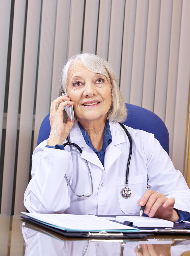 Doctor making phone call with smartphone stock images