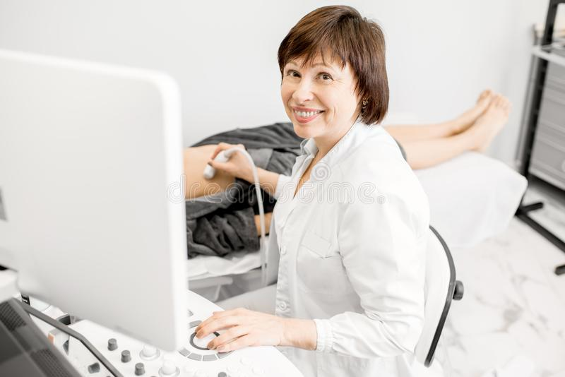 Doctor making ultrasound examination to a young woman. Portrait of a senior doctor during an ultrasound examination to a young women patient stock photography
