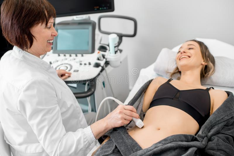 Doctor making ultrasound examination to a young woman. Senior doctor making an ultrasound examination to a young women patient royalty free stock images