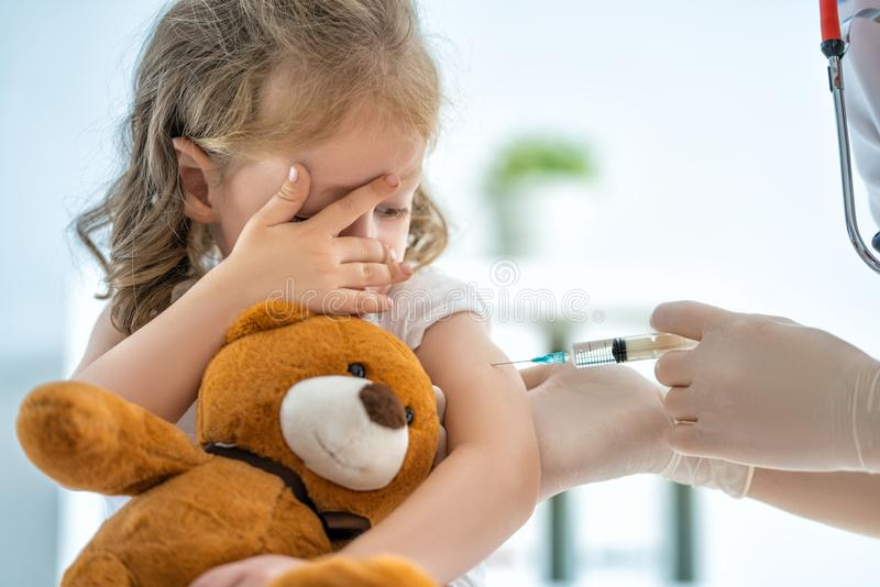 Vaccination to a child. A doctor making a vaccination to a child royalty free stock image