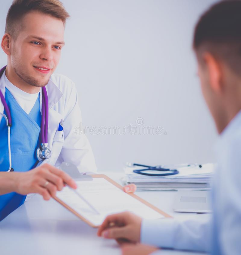 Doctor male giving patient folder with paper in her office, isolated. Doctor male giving patient folder with paper in her office stock photos