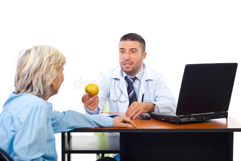 Download Doctor Male Offering Apple To Senior Stock Photo - Image: 16512054