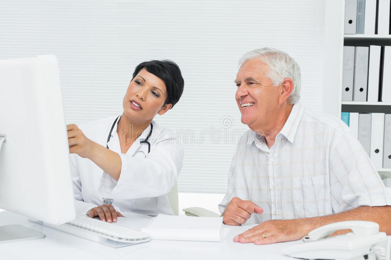 Doctor with male patient reading reports on computer stock images