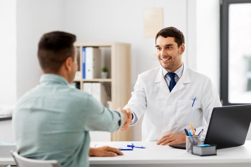 Doctor and male patient shaking hands at hospital. Medicine, healthcare and people concept - smiling doctor and male patient shaking hands at hospital stock photos