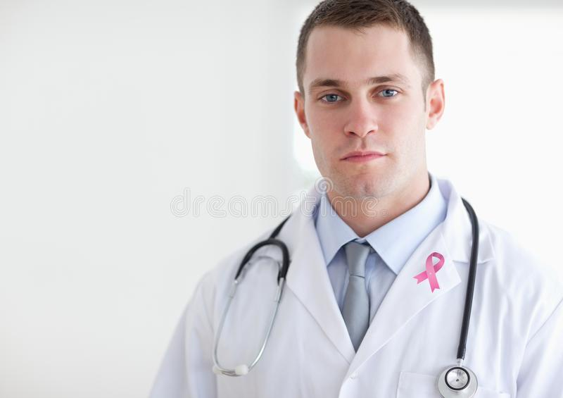 Doctor man with breast cancer awareness ribbon. Digital composite of Doctor man with breast cancer awareness ribbon royalty free stock photo