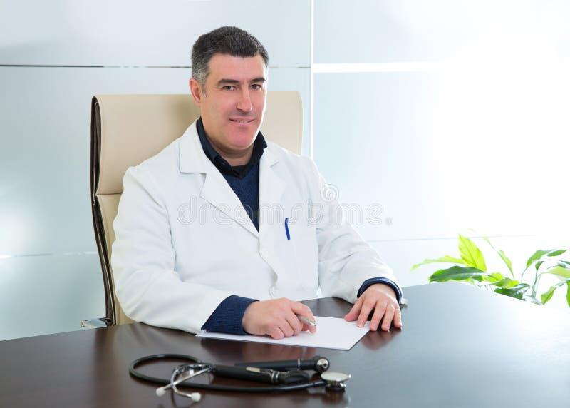 Doctor man sitting in hospital office desk portrait