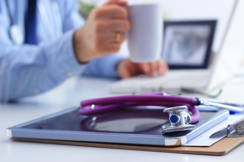 Doctor man with medical stethoscope sitting at the desk in the office and using laptop stock photos
