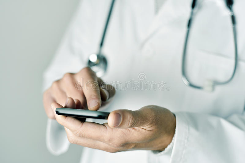 Doctor man using a smartphone. Closeup of a young caucasian doctor man wearing a white coat using a smartphone stock images