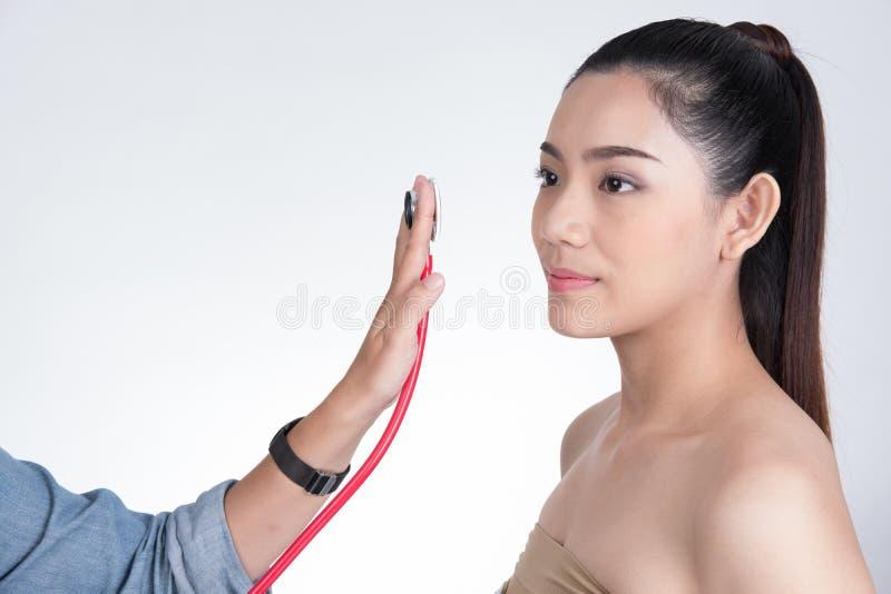 doctor& x27; mano de s que sostiene el estetoscopio para el woman& x27 del chequeo; cara de s foto de archivo
