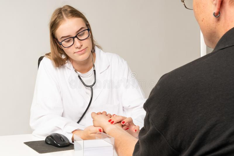 A doctor manually measures the pulse on a patient`s wrist stock photography