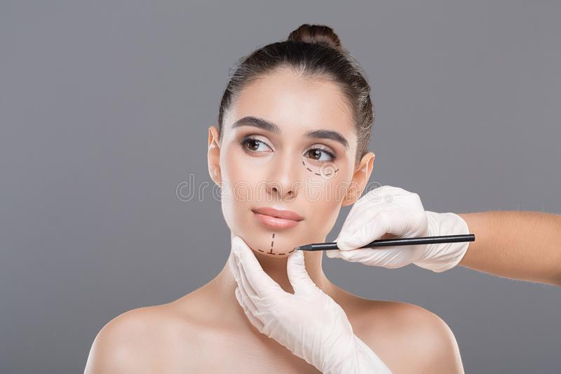 Doctor marking young woman face before cosmetic surgery. On gray background stock photo