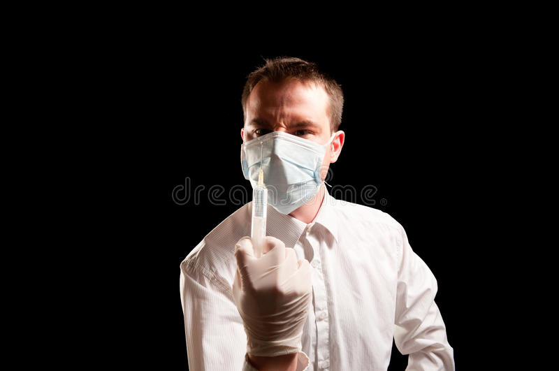 Doctor with mask and syringe royalty free stock photography