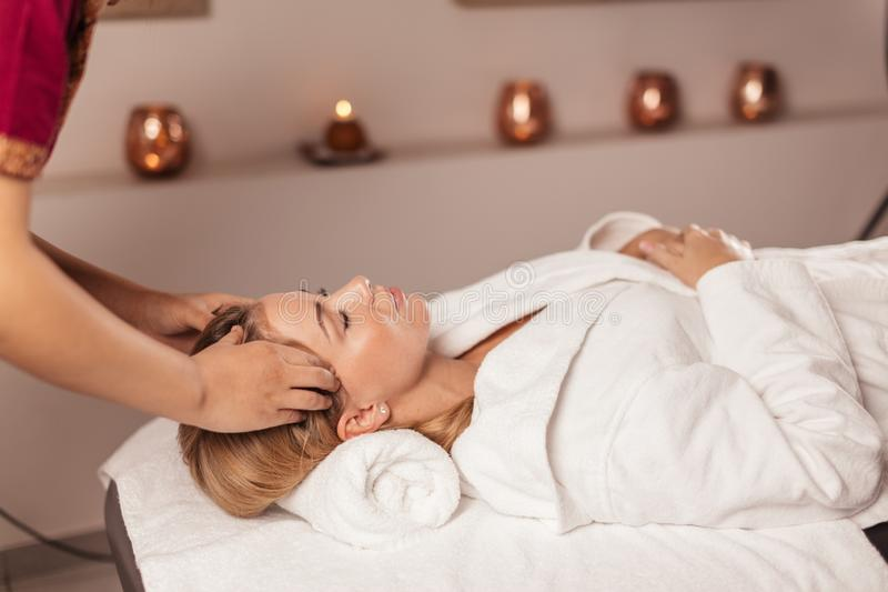 Doctor massaging a woman`s temples royalty free stock image