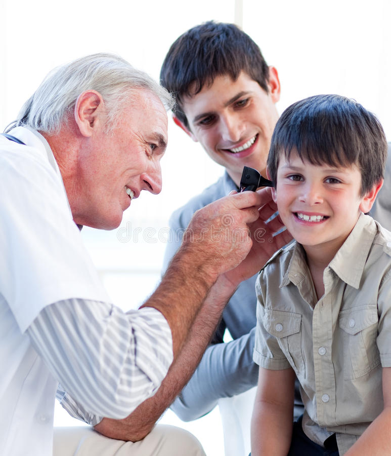 Doctor mayor que examina los oídos de un niño pequeño imagen de archivo libre de regalías